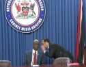 Communications Minister Stuart Young whispers something to Prime Minister Dr Keith Rowley before the start of the Post Cabinet media briefing May 23, 2019.