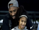 FILE - In this July 26, 2018, file photo former Los Angeles Laker Kobe Bryant and his daughter Gianna watch during the U.S. national championships swimming meet in Irvine, California.  (AP Photo/Chris Carlson,File)