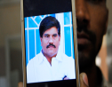 An employee of a local television channel shows a picture of slain journalist Aziz Memon on his mobile, after a demonstration to condemn his killing, in Hyderabad, Pakistan, Monday, February 17, 2020.  (AP Photo/Pervez Masih)