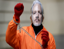 A demonstrator supporting Julian Assange wears a mask and chains outside Westminster Magistrates Court in London, Thursday, Jan. 23, 2020. Assange is scheduled to be presented before the court by videolink, for a case management hearing ahead of his full extradition trial which begins on Feb. 24. (AP Photo/Kirsty Wigglesworth)
