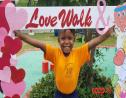 Rakenzie Pierre-Calendar holding the Love Walk and Health Fair photo frame.