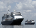 The Zaandam cruise ship, left, carrying some guests with flu-like symptoms, is anchored shortly after it arrived to the bay of Panama City, Friday, March 27, 2020, amid the worldwide spread of the new coronavirus. Health authorities are expected to board the ship to test passengers and decide whether it can cross the Panama Canal. (AP Photo/Arnulfo Franco)