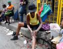 In this AP file photo taken February 15, 2011, a woman applies skin lightening cream to her legs in downtown Kingston.